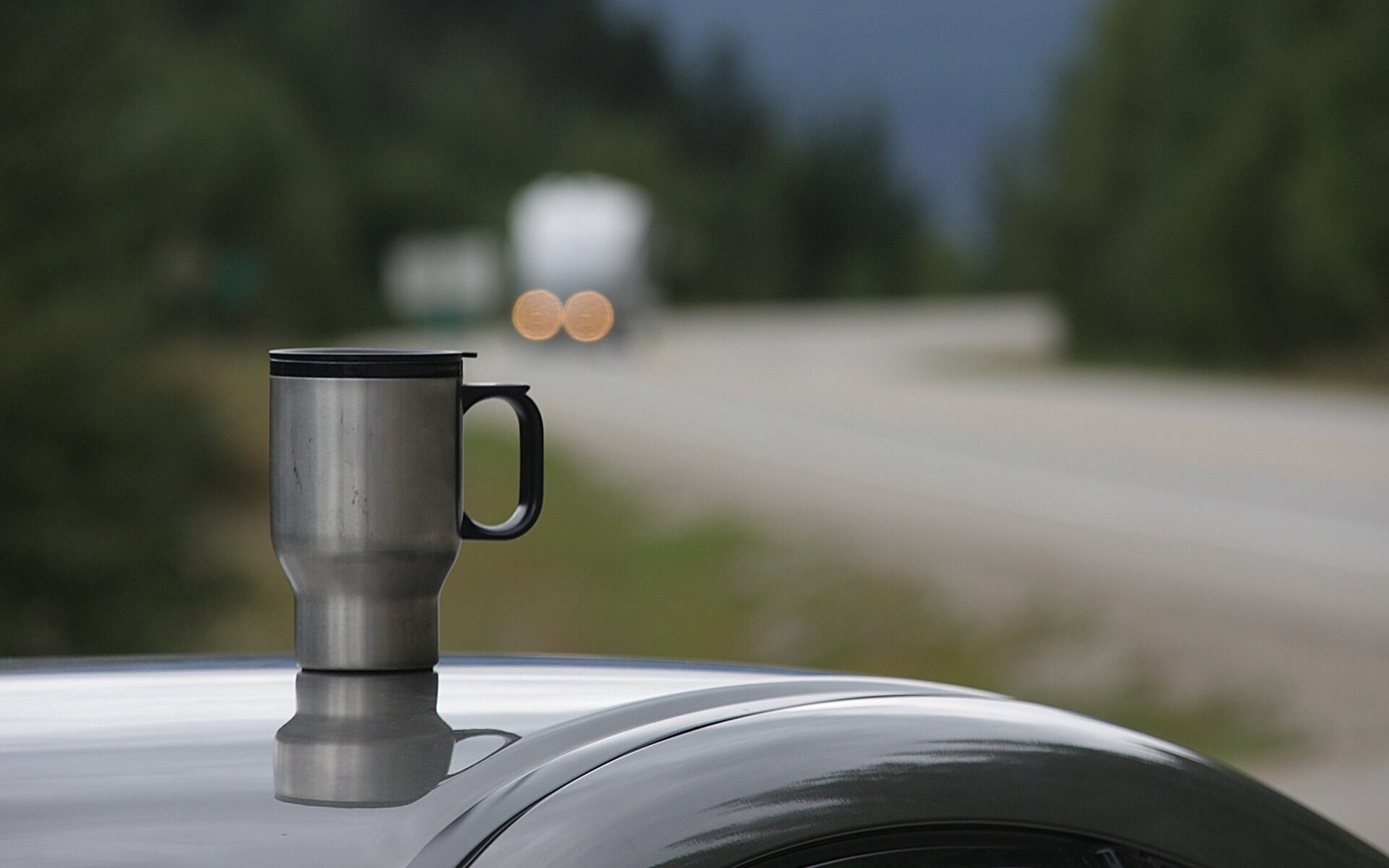 a travel mug siting on top of a car